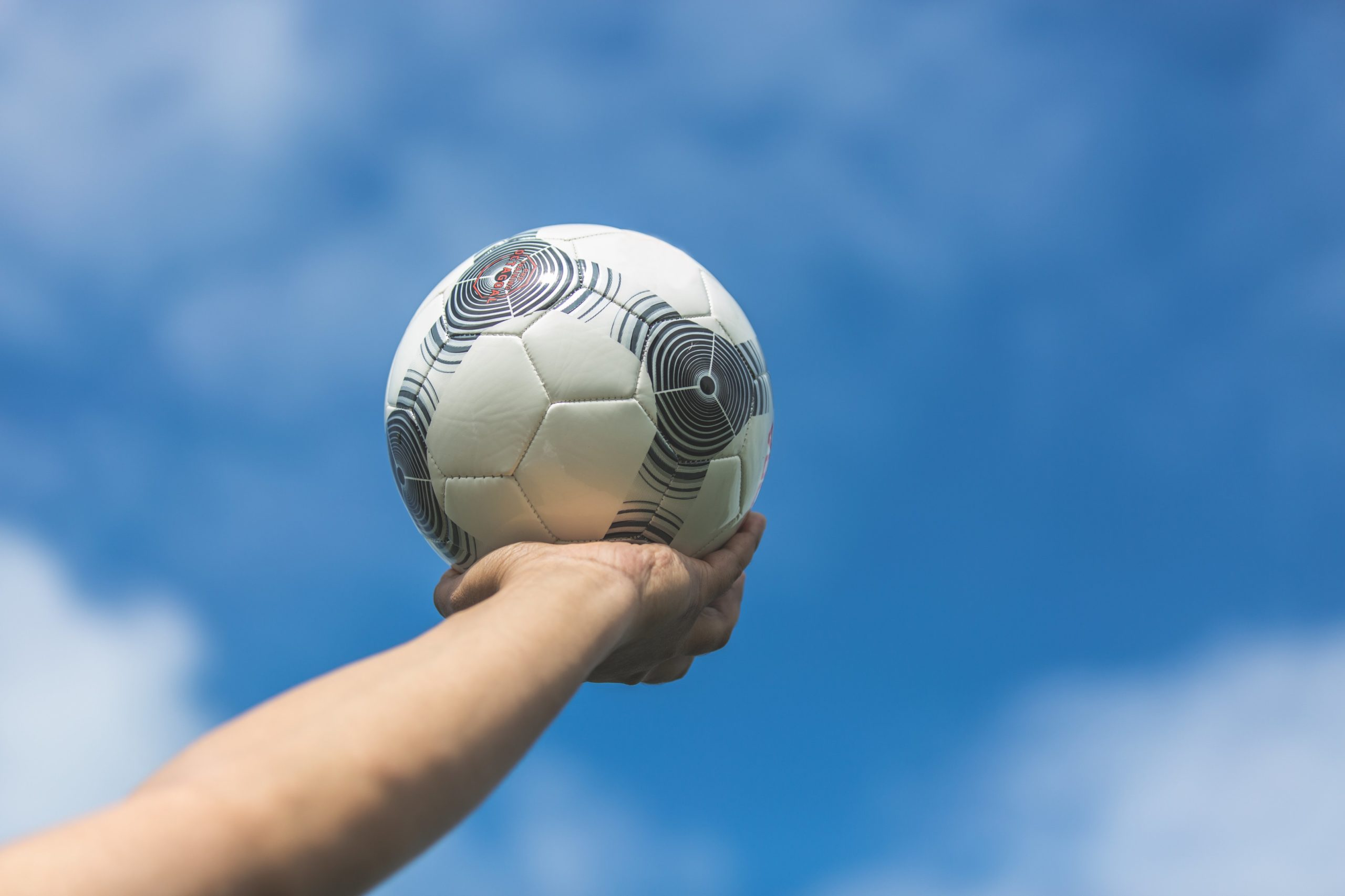 holding-out-soccer-ball-to-the-blue-sky